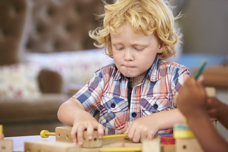 Зрачок Montessori работая на столе с деревянными формами стоковое фото