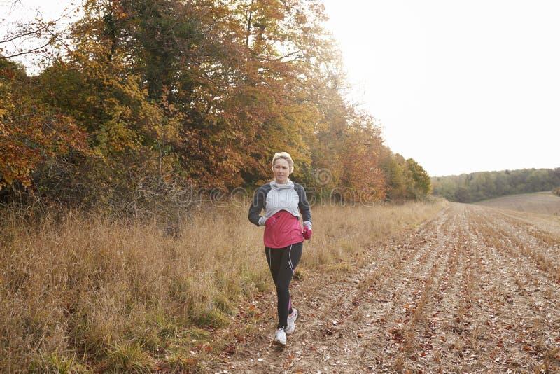 Зрелая женщина бежать вокруг поля осени стоковая фотография rf