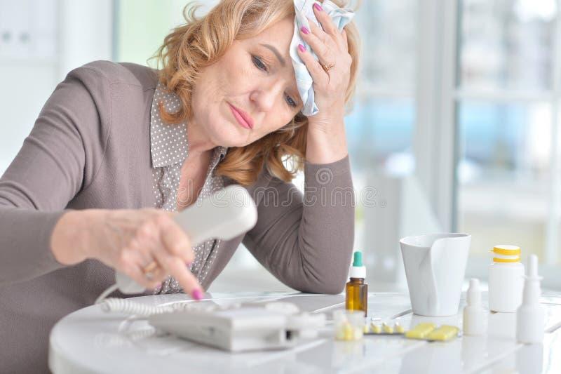 Зрелая женщина вызывая доктора стоковые изображения rf