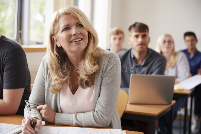 Зрелая женщина в коллеже присутствуя на классе обучения взрослых стоковое фото