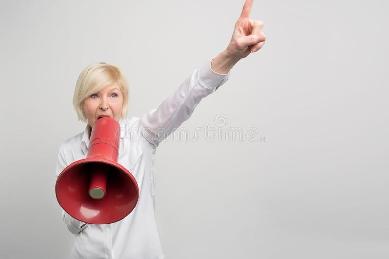 Зрелая женщина держит мегафон близко к ее рту и sreaming в ее Она защищает права человека На стоковые фотографии rf