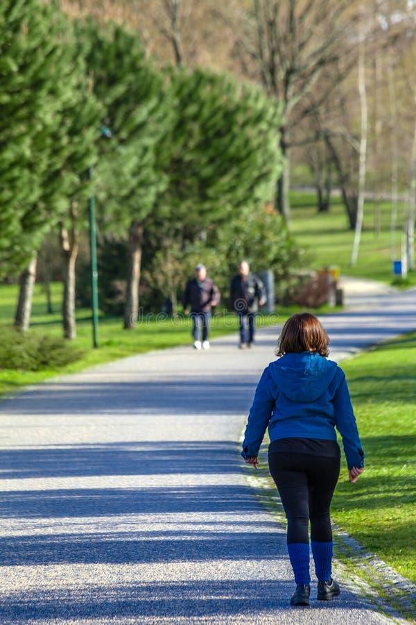 Зрелая женщина идя для прогулки фитнеса в парке Parque da Devesa городском стоковые изображения