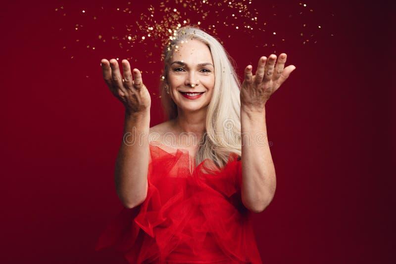 Зрелая женщина имея потеху с яркими блесками стоковая фотография