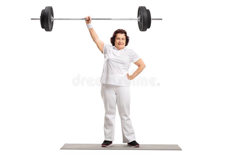 Зрелая женщина на стоять на циновке тренировки и поднимать barbel стоковые изображения rf