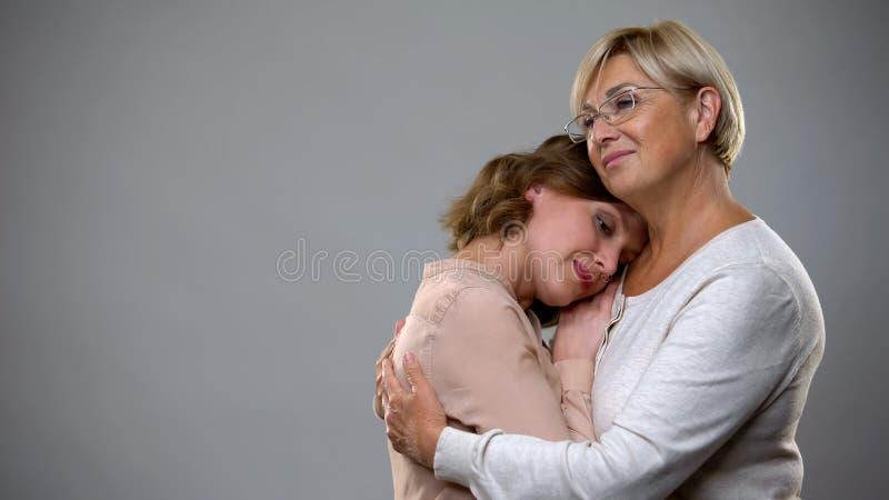 Зрелая женщина обнимая взрослую дочь на серой предпосылке, поддержке материнства стоковые изображения rf