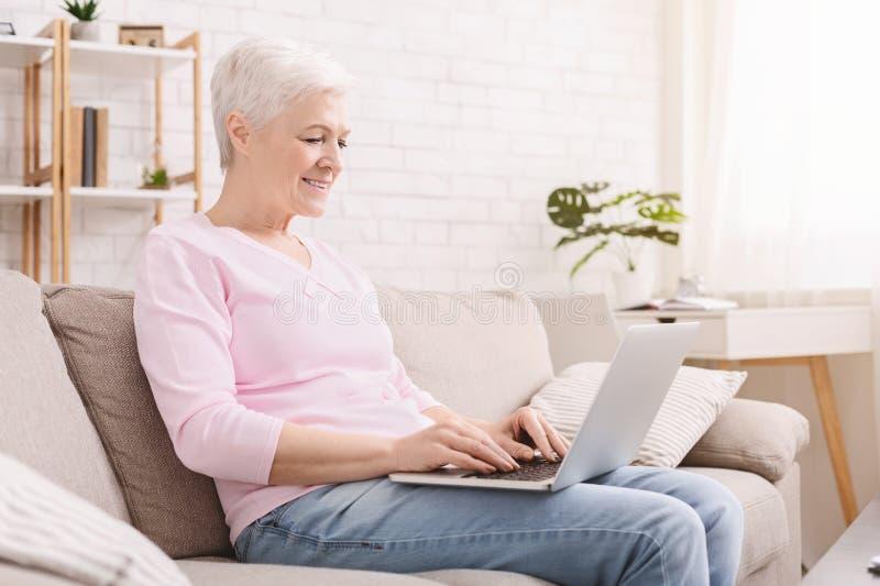 Зрелая женщина печатая на ее ноутбуке стоковые изображения rf