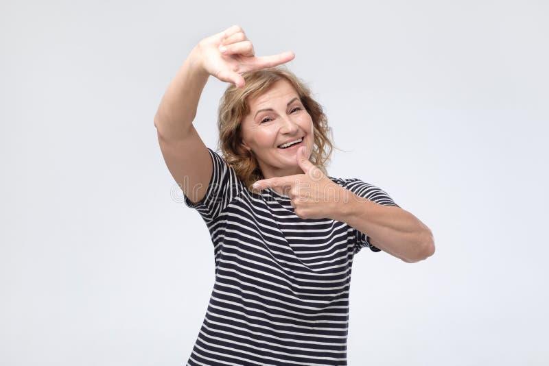 Зрелая женщина смотря камеру и показывая жестами рамка пальца стоковое фото