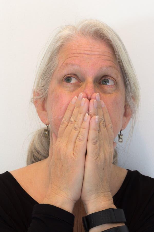 Зрелая женщина с руками над ртом смотря вверх и отсутствующим, естественный отсутствие состава, нейтральной предпосылки стоковое изображение rf