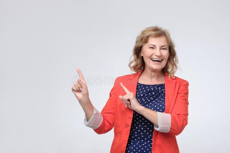 Зрелая женщина усмехаясь широко, указывая пальцы прочь, показывая что-то интересное и возбуждая стоковое изображение