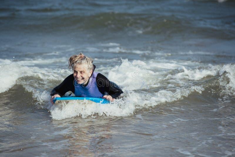 Зрелая женщина Bodyboarding в море стоковое фото