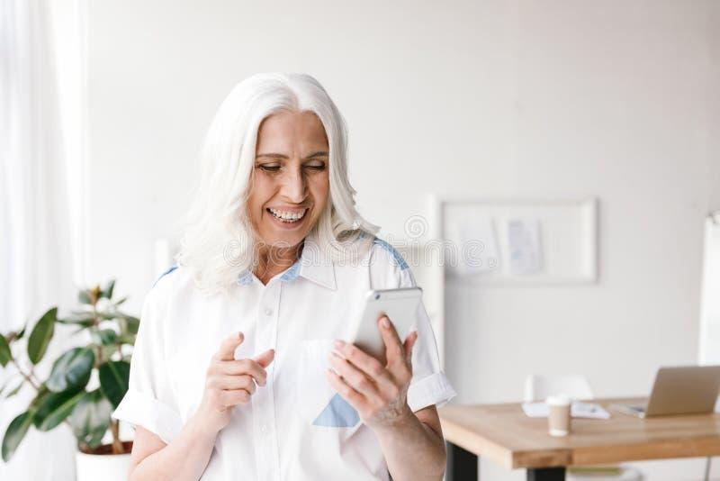 Зрелая жизнерадостная женщина внутри помещения в офисе стоковое фото rf