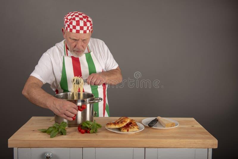 Зрелая итальянская плакировка шеф-повара вверх по блюду макаронных изделий стоковые фотографии rf