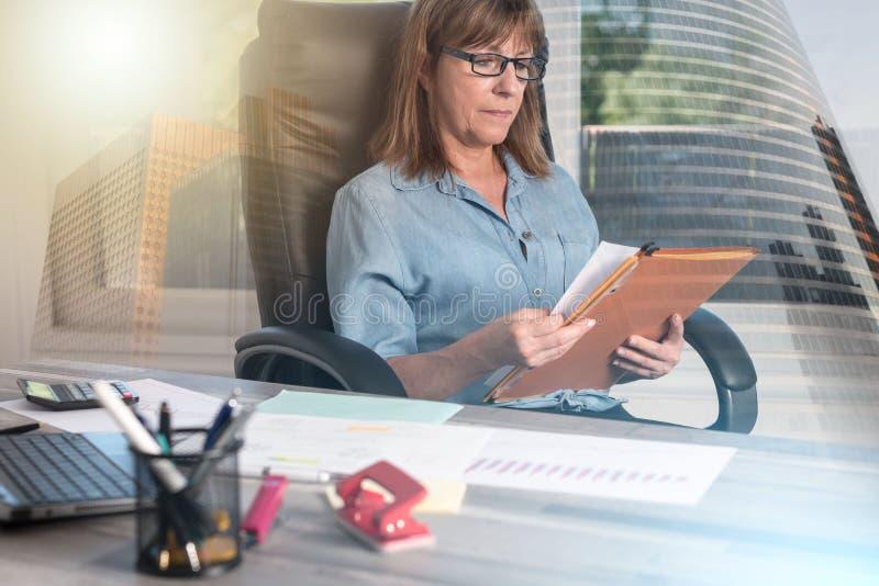 Зрелая коммерсантка проверяя документы; множественная выдержка стоковая фотография