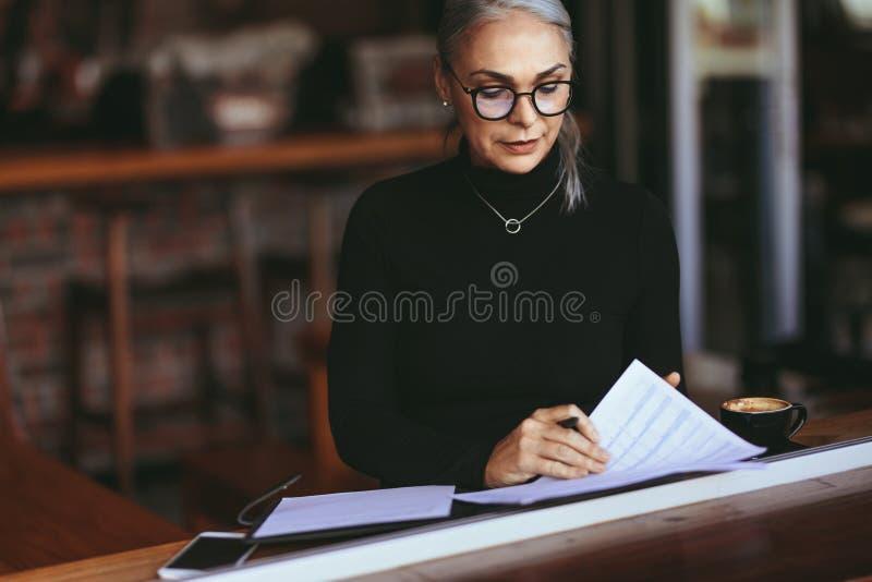 Зрелая коммерсантка читая некоторую обработку документов на кафе стоковое изображение rf