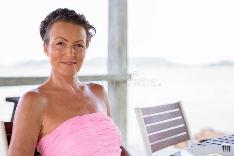 Зрелая красивая туристская женщина на пляжном комплексе стоковое изображение