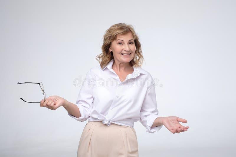 Зрелая, милая женщина усмехаясь к камере r стоковые фотографии rf