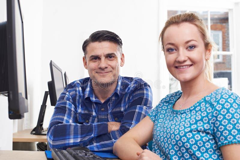 Зрелая молодая женщина тренировки человека на компьютере в офисе стоковые изображения