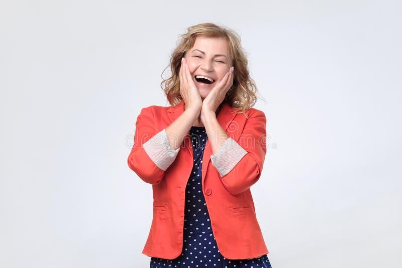 Зрелая счастливая женщина смеясь громко на шутке стоковая фотография rf