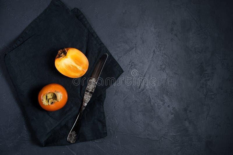 Зрелая хурма, нож на черной предпосылке с космосом для текста стоковое фото