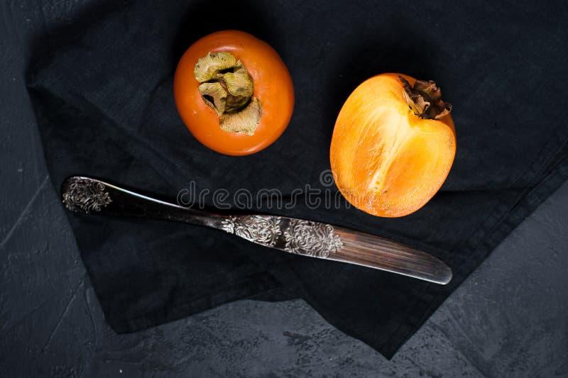 Зрелая хурма, нож на черной предпосылке с космосом для текста стоковое фото rf