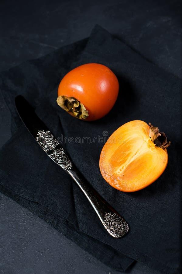 Зрелая хурма, нож на черной предпосылке с космосом для текста стоковые фотографии rf