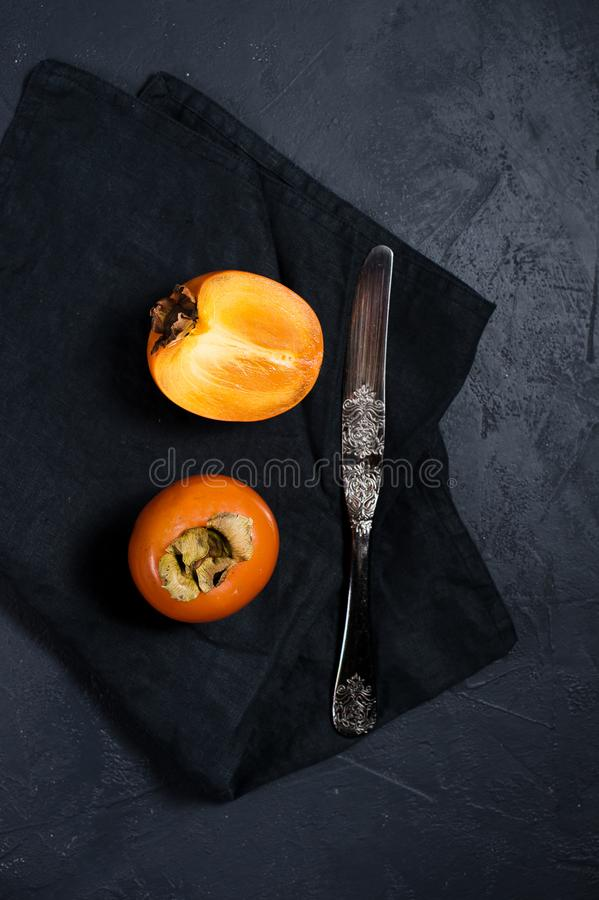 Зрелая хурма, нож на черной предпосылке с космосом для текста стоковые изображения