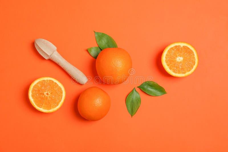 Зрелые апельсины, листья и деревянный juicer на предпосылке цвета Апельсины взгляда сверху зрелые, листья и деревянный juicer на  стоковые изображения rf
