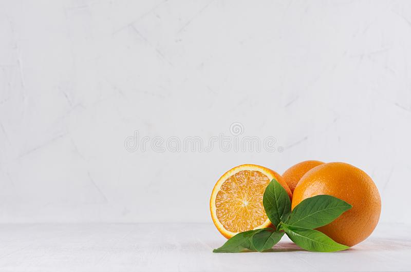 Зрелые апельсины с зелеными молодыми листьями и кусок сока на белой предпосылке перспективы стоковое фото