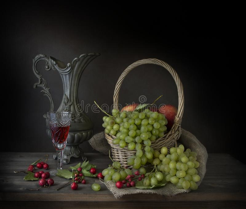 Зрелые виноградины, бокал вина и ягоды осени на таблице стоковое фото