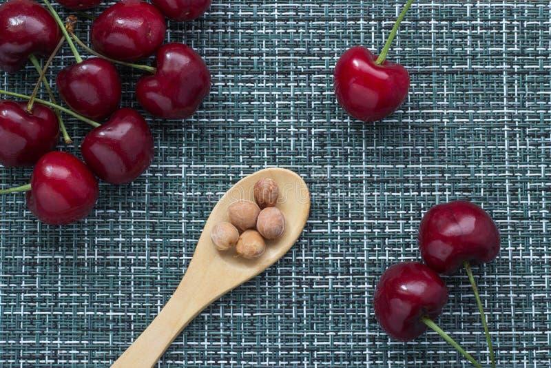 Зрелые вишни на плетеной предпосылке и деревянной ложке снизу с стерженями ягод, 3 ягодами отдельно на праве, cl стоковое изображение rf