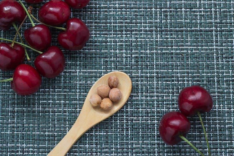 Зрелые вишни на плетеной предпосылке и деревянной ложке снизу с стерженями ягод, 2 ягодами отдельно на праве стоковые изображения rf