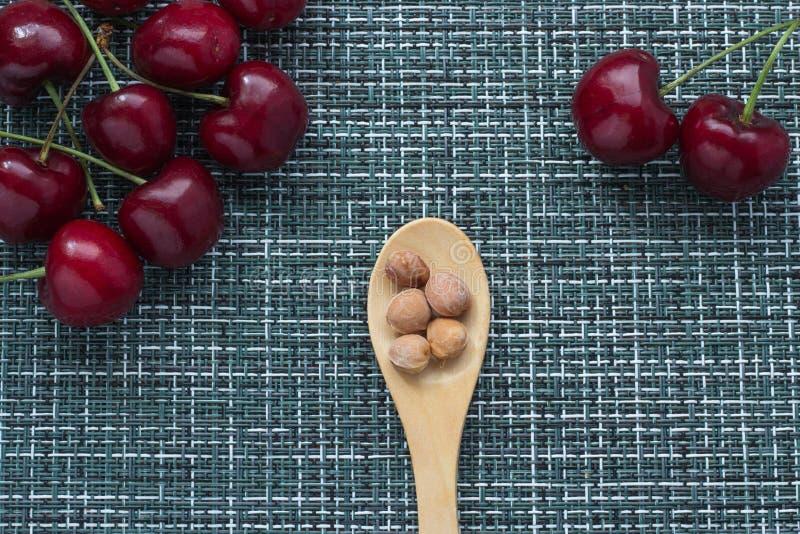 Зрелые вишни на плетеной предпосылке и деревянной ложке снизу с стерженями ягод, 2 ягодами отдельно на праве, clos стоковые фотографии rf