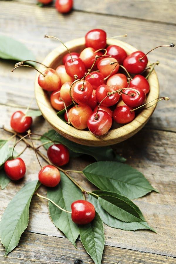 Зрелые вишни с листьями на деревянной предпосылке, в деревянном pl стоковое фото