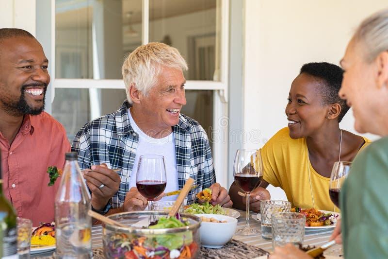 Зрелые друзья наслаждаясь обедом совместно стоковое фото