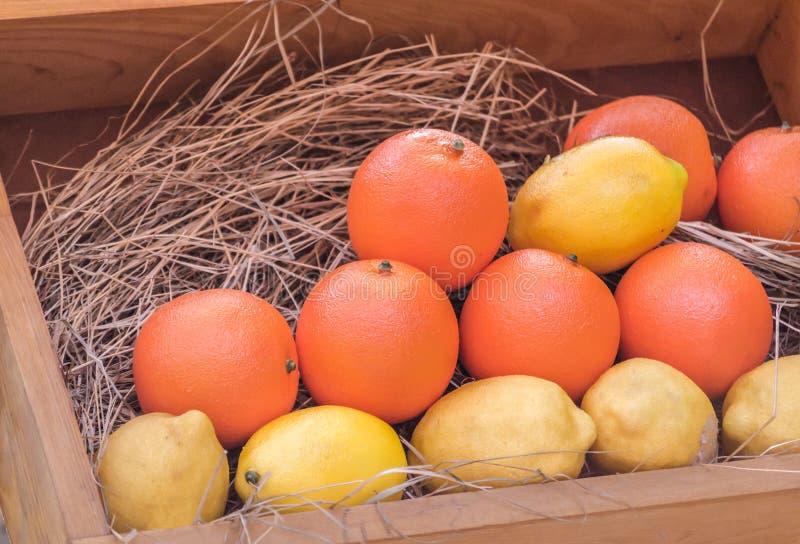 Зрелые желтые лимоны и оранжевые апельсины в деревянной коробке стоковые фото