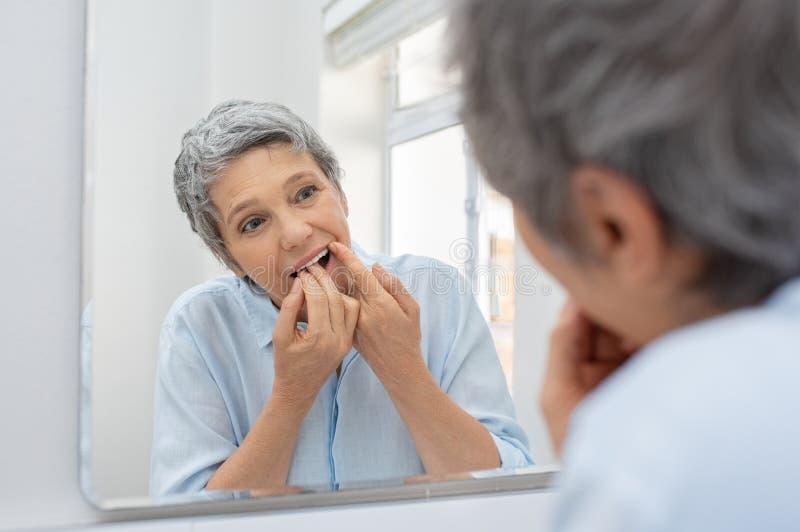 Зрелые зубы чистки женщины с зубочисткой стоковое изображение rf