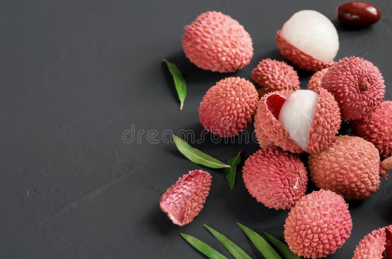 Зрелые красные ягоды lychee плоско кладут на черную предпосылку скопируйте космос стоковые фотографии rf