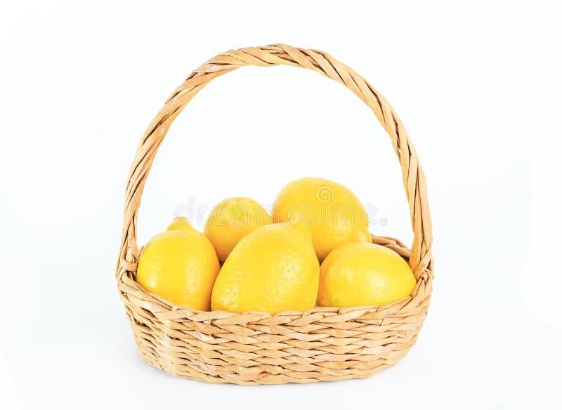 Зрелые лимоны в плетеной корзине на белизне изолировали предпосылку стоковое изображение