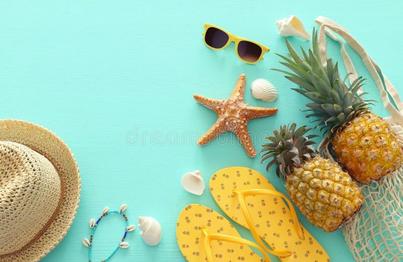 Зрелые объекты стиля морской жизни ананаса и пляжа над предпосылкой пастельной мяты голубой деревянной Тропическая концепция летн стоковое фото rf
