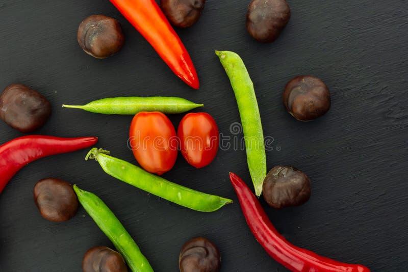 Зрелые овощи зеленеют смешивание вишни томата перца красного chili стручка гороха свежее на черном основании дизайна предпосылки стоковые изображения rf