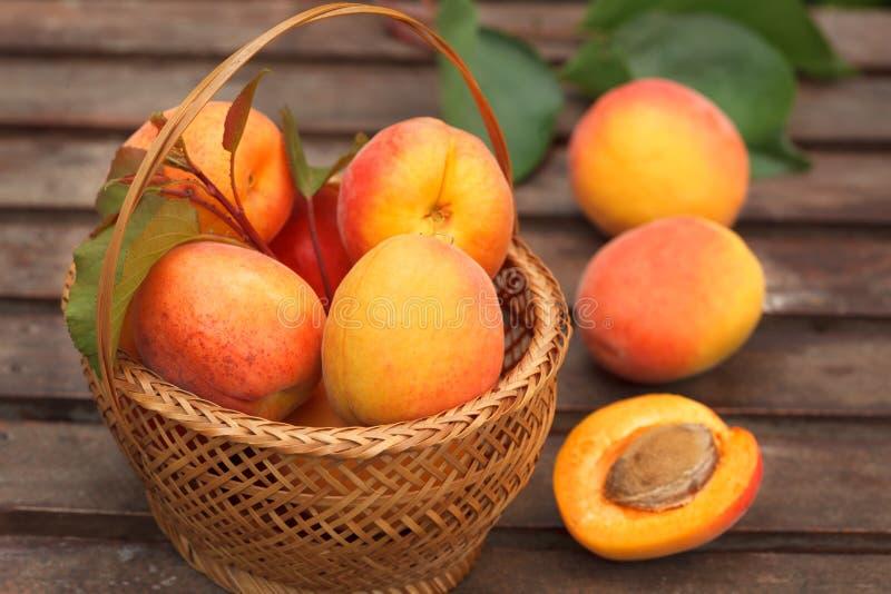 Зрелые органические абрикосы в плетеной корзине со свежими листьями на деревянном столе стоковая фотография