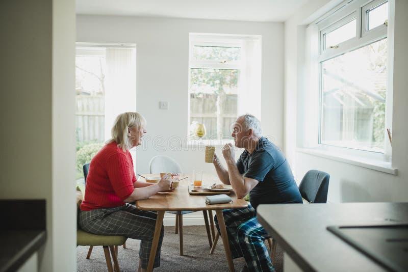 Зрелые пары наслаждаясь завтраком дома стоковые изображения rf