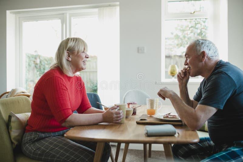 Зрелые пары наслаждаясь завтраком дома стоковое изображение