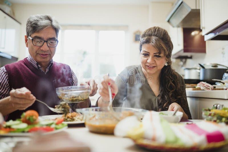 Зрелые пары наслаждаясь обедающим дома стоковые фото