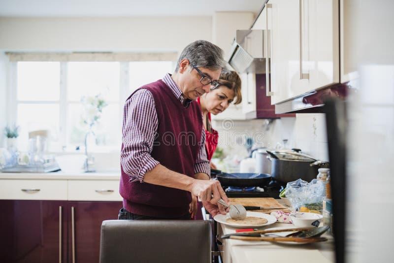 Зрелые пары подготавливая Chapati совместно стоковое фото