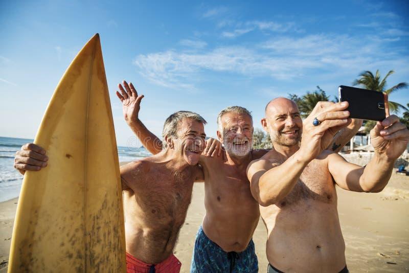 Зрелые серферы на пляже стоковые изображения