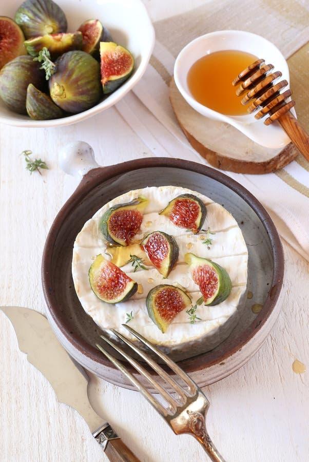 Зрелые смоквы, сыр камамбера и мед стоковые фото