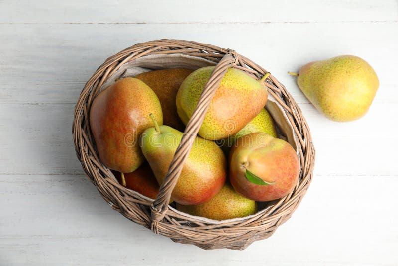 Зрелые сочные груши в плетеной корзине на белом деревянном столе, выше стоковая фотография rf