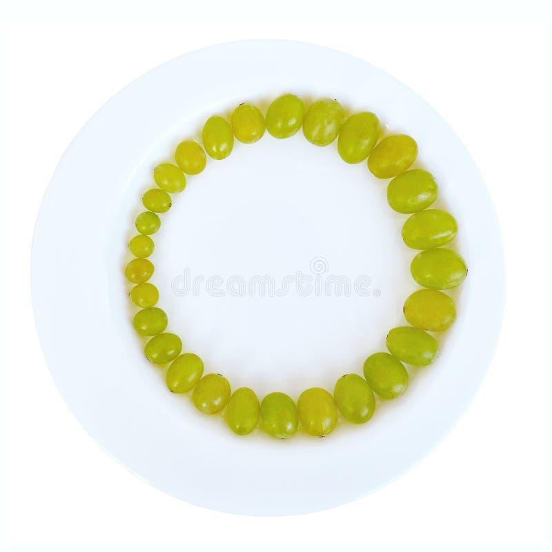 Зрелые сочные зеленые виноградины выровнялись с кольцом в порядке увеличивая размера ягод в белой плите, изолированным взгляд све стоковые изображения