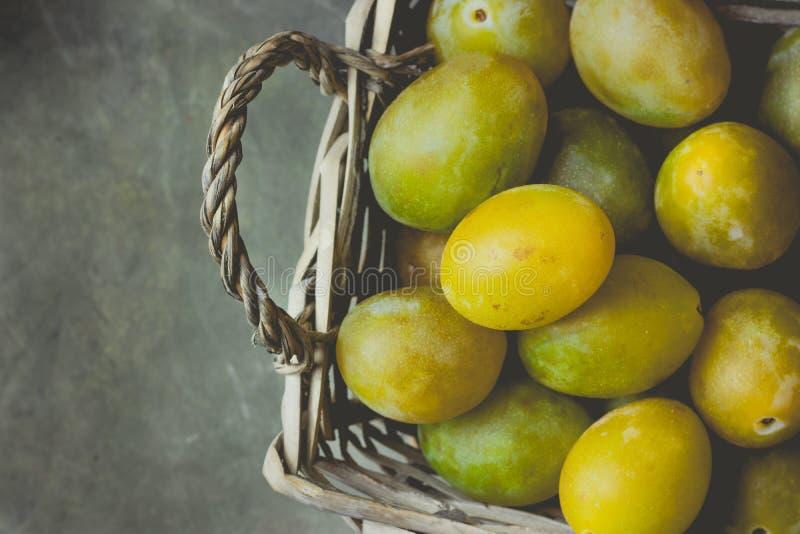 Зрелые сочные красочные желтые и зеленые сливы в плетеной корзине Темная конкретная каменная предпосылка Сбор падения осени, благ стоковая фотография